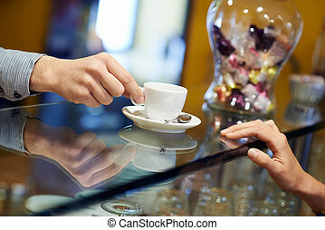 people in cafeteria with bartender serving espresso coffee