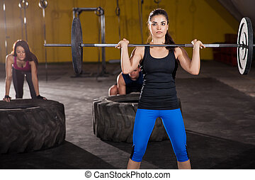 Crossfit training at a gym - Three people working out in a...