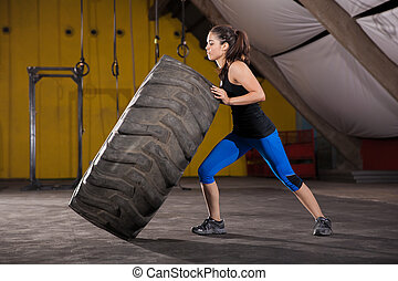 Tire flip with no effort - Strong brunette making almost no...