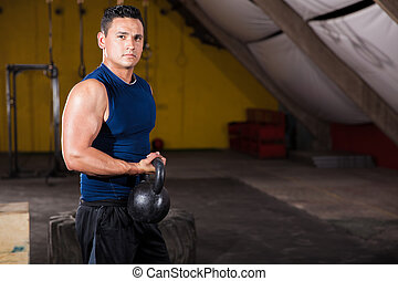 Enjoying my crossfit workout - Strong young man lifting a...
