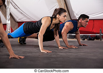 Focused on her push ups - Beautiful young brunette doing...