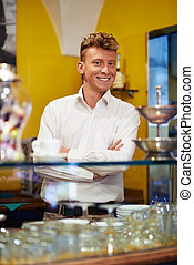 People in cafeteria, portrait of happy young man working as barman, smiling at camera behind counter