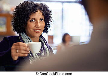 People in bar with woman drinking espresso coffee
