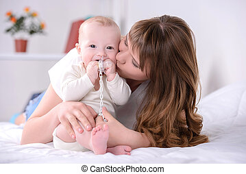 Baby and Mom - happy mom and baby playing on the bed at home