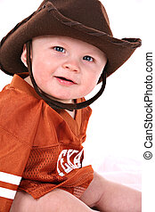 happy smiling 6-month old baby boy portrait wearing cowboy...