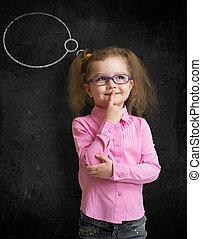 Funny child in eyeglasses standing near school chalkboard...