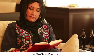 Muslim woman reading book - Muslim woman sitting on sofa and...