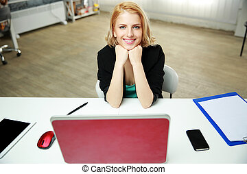 Young cheerful woman sitting at her work place