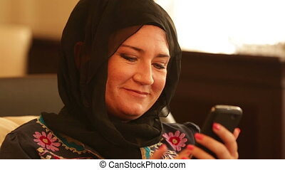 Muslim woman sending text message