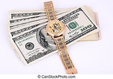 stack of 100 dollar bills and gold watch on a light background