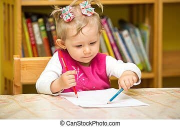 Cute child girl drawing with colorful pencils in preschool at the table in kindergarten