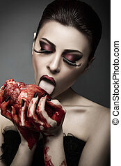 Beauty young woman licks blood from human heart against grey...