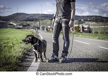 Man walking his dog on the road in Spain