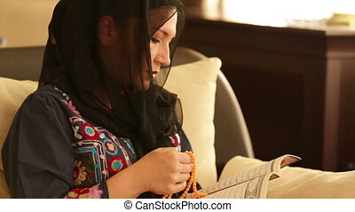 Muslim woman praying and reading koran