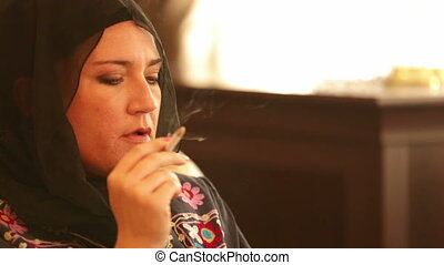 Sad muslim woman smoking