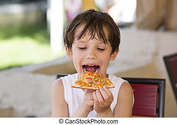 boy eating pizza in a restaurant