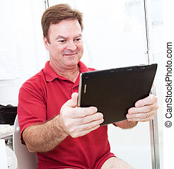 Tablet PC in Bathroom - Man reading a tablet pc while using...