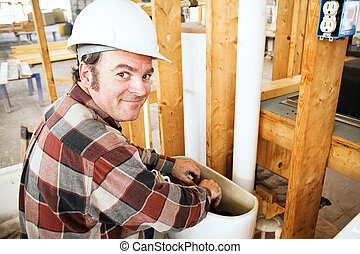 Plumber on Construction Site - Plumber installing a toilet...
