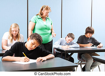 Supervised Testing in School - Teacher supervising high...