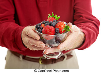 Bowl of Healthy Berries - Closeup of senior man's hands...