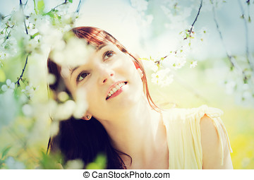 Natural, beautiful woman relaxing and smiling in a spring garden.