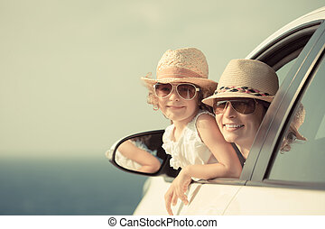 Happy woman and child in car against sea and sky background....