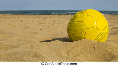 Yellow ball on the sand