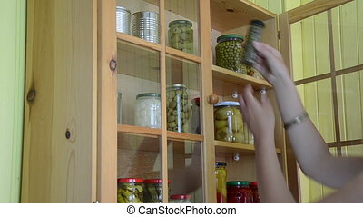 two jar caper garlic - girl from a wooden cupboards with...