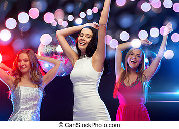 three smiling women dancing in the club - new year,...