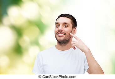 smiling young handsome man pointing to cheek - health and...
