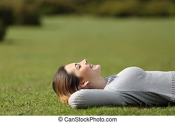 Beautiful woman resting on the grass in a park