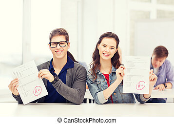 two teenagers holding test or exam with grade A - education,...