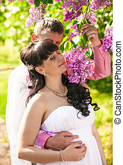 portrait of beautiful bride smelling lilac flowers with...