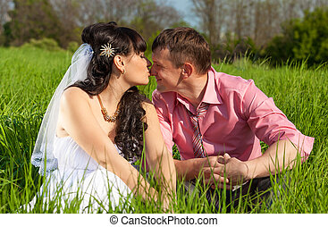 bride and groom kissing in lips while sitting on meadow -...