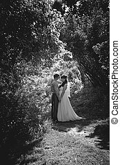 Monochrome photo of bride and groom kissing under high trees