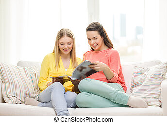 two girlfriends reading magazine at home - friendship and...