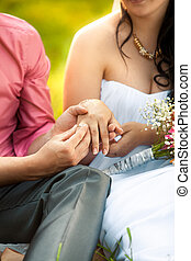 groom putting golden ring in brides hand at park - Closeup...