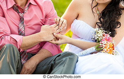 photo of young bride putting wedding ring on grooms hand