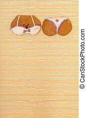 Yellow pink bikini shape gingerbread cake cookie on bamboo...