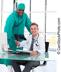 Doctor and surgeon smiling at the camera with an X-ray -...