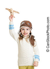 kid girl dressed pilot helmet and playing with wooden airplane toy