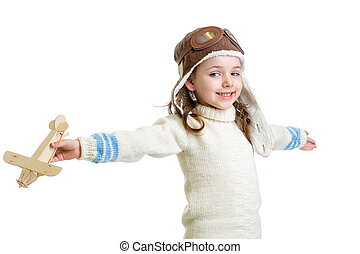 kid dressed as pilot and playing with wooden airplane toy isolated on white background