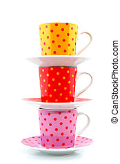 speckles cups and saucers isolated over white