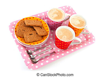 speckles cups and saucers with cookies isolated over white