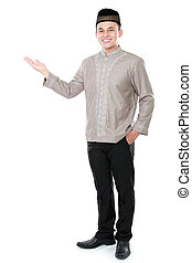 smiling asian muslim man presenting copy space isolated over...