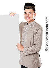 smiling asian muslim man holding blank board isolated over...