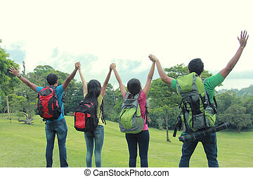 group of friends on a hiking raise their hand together - A...