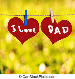 I love Dad message on Red heart shape on note paper attach to rope with clothes pins on yellow bokeh background