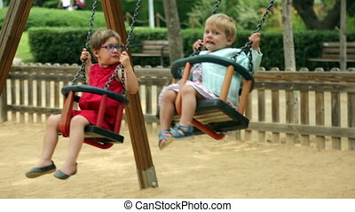 Laughing children on swing in summer park