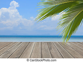 Wood plank over beach with coconut palm tree leaf